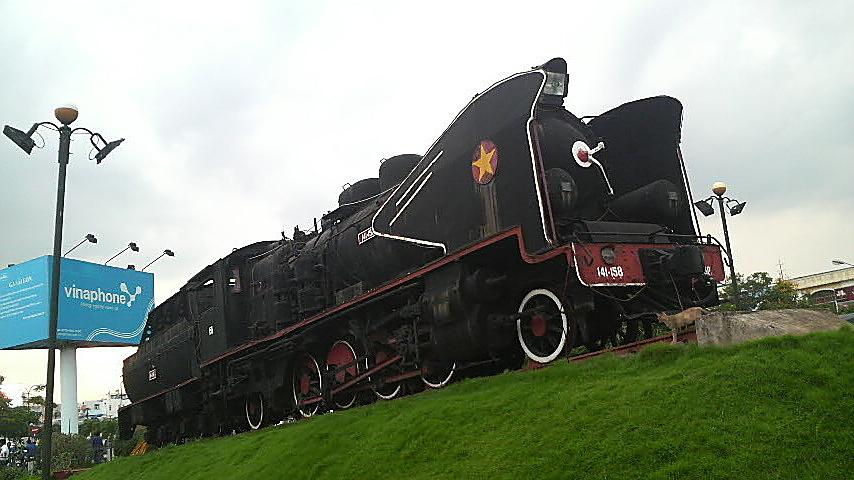 Old train engine on proud display outside Saigon Railway Station, Vietnam