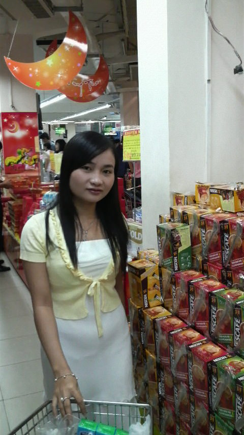Nga in the coffee and milk goods section of local Coop Mart, a bundle of green tea flavored milk cartons in her trolley