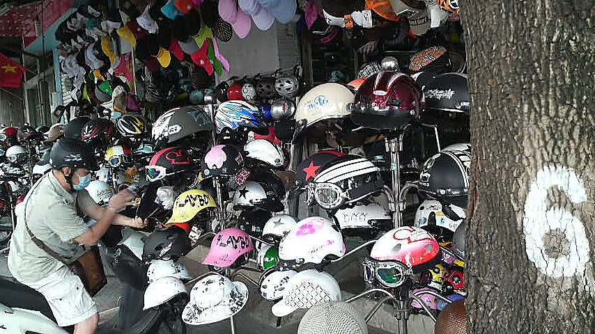 Helmets, goggles and hats for sale in a streetside Saigon shop