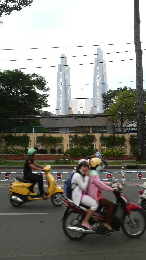Twin spires and clockface of a church under construction near the Saigon Racetrack.